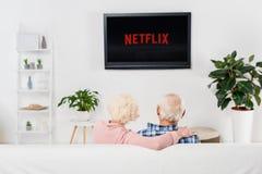 tillbaka sikt av hållande ögonen på netflix för höga par på tv arkivbild
