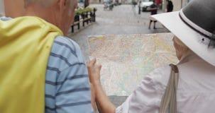 Tillbaka sikt av höga turister som går med en översikt i händer som söker efter rutten lager videofilmer