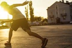 Tillbaka sikt av idrottsman nen för ung man i tillfällig konturspring i den stads- staden på en solnedgång arkivbild