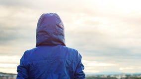 Tillbaka sikt av idrottsman nenkvinnan som ser solnedgång över stadshorisont, når att ha övat Motivation-, sport- och konditionli arkivfoton