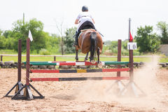 Tillbaka sikt av idrottsmannen på hästen som hoppar över barriär royaltyfri fotografi