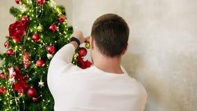 Tillbaka sikt av innehavet för ung man som hänger en boll på en fauxjulgran jul som dekorerar den home treen långsam rörelse stock video