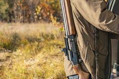 Tillbaka sikt av jägaren att bära klassisk gevärshotgu i skog f arkivfoto