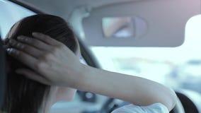 Tillbaka sikt av kvinnachauffören som trycker på en spegel för bakre sikt och korrigerar frisyren, medan köra bilen arkivfilmer