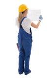Tillbaka sikt av kvinnan i enhetligt hållande byggnadsplan för blå byggmästare Arkivbild
