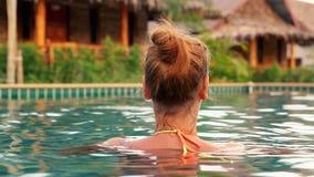 Tillbaka sikt av kvinnan i simbassäng