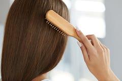 Tillbaka sikt av kvinnan med sunt långt hår som borstar den med borsten Royaltyfria Bilder