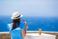 Tillbaka sikt av kvinnan som dricker kallt kaffe som tycker om havssikt Den härliga kvinnan kopplar av under europeisk havssemest Royaltyfria Bilder