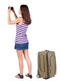Tillbaka sikt av kvinnan som fotograferar som reser med suitcas Royaltyfri Bild