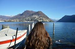 Tillbaka sikt av kvinnan som går på pir med vinterkläder, sjö Lugano, Schweiz, Europa arkivfoto