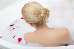 Tillbaka sikt av kvinnan som kopplar av i bad med röda blommakronblad Arkivbild