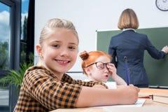 tillbaka sikt av lärarehandstil på den svart tavlan medan studera för studenter arkivfoto