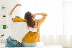 Tillbaka sikt av lesbiska lyckliga par för kvinnor som vaknar upp i morgon och att sitta på säng och att sträcka i det hemtrevlig Royaltyfri Foto