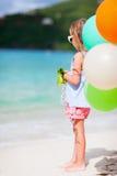 Tillbaka sikt av lilla flickan med ballonger på stranden Arkivfoton