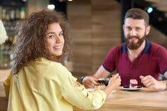 Tillbaka sikt av lockigt flickasammanträde i kafé med pojkvännen som äter kakan royaltyfri foto