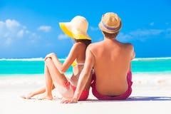 Tillbaka sikt av lyckliga unga caucasian par i hattar som sitter på stranden Arkivbilder