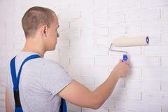 Tillbaka sikt av manmålaren i workwearmålningvägg med målarfärgro royaltyfri bild