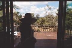 Tillbaka sikt av mannen för hatt för ung kvinna den bärande ledande på balkong eller terrassen med tropiska Forest Landscape Royaltyfria Foton