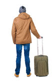 Tillbaka sikt av mannen i ett brunt omslag med resväskan Royaltyfria Bilder