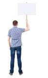 Tillbaka sikt av mannen som visar ett teckenbräde Fotografering för Bildbyråer