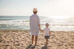 Tillbaka sikt av modern och sonen på stranden på den soliga dagen sätta på land barn för white för semestern för sanden för famil Arkivbild