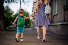 Tillbaka sikt av modern som lite går med sonen med en ryggsäck arkivbilder