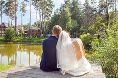 Tillbaka sikt av nygifta personer som sitter på träpir nära sjön på soligt arkivfoton