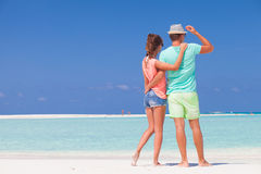 Tillbaka sikt av par i ljus kläder som kramar på Fotografering för Bildbyråer