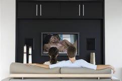 Tillbaka sikt av par som håller ögonen på romantisk film på television i vardagsrum fotografering för bildbyråer