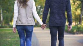 Tillbaka sikt av par som rymmer händer och går säkert i ljus framtid lager videofilmer