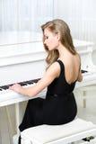 Tillbaka sikt av pianistsammanträde och spelapianot Royaltyfria Bilder