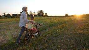 Tillbaka sikt av pojken som lär att rida cykeln med farmodern lager videofilmer