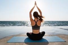 Tillbaka sikt av praktiserande yogasammanträde för ung attraktiv flicka i PA royaltyfri bild
