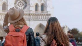 Tillbaka sikt av resande kvinna två med ryggsäcken som går nära Notre Dame, berömd domkyrka i Paris, Frankrike lager videofilmer