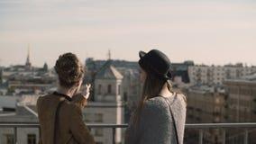 Tillbaka sikt av stilfull ung kvinna som två tycker om den härliga panoramautsikten av staden och talar som pekar med fingret arkivfilmer