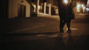 Tillbaka sikt av stilfulla par som tillsammans går i stadsmitten i aftonen Man och kvinna på romantiskt datum arkivfilmer