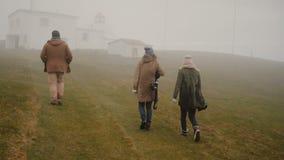 Tillbaka sikt av tre unga handelsresande som fotvandrar i bergdalen i dimmig dag Vänner som går till och med fältet arkivfilmer