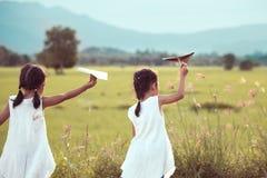 Tillbaka sikt av två asiatiska barnflickor som spelar det pappers- flygplanet för leksak Arkivbild