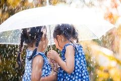 Tillbaka sikt av två asiatiska små flickor med paraplyet Arkivbilder