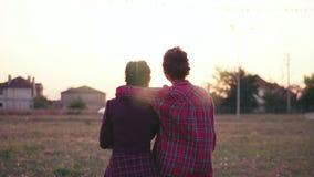 Tillbaka sikt av två bästa vän som kramar sig Lycklig för kramvisning för ung kvinna förälskelse och affektion Slowmotion skott stock video