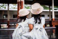 Tillbaka sikt av två gulliga asiatiska små flickor som väntar på drevet Royaltyfri Bild