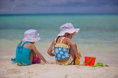 Tillbaka sikt av två lilla systrar i trevliga baddräkter Arkivfoton