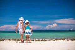 Tillbaka sikt av två lilla systrar som ser havet Arkivfoto