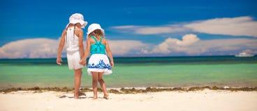 Tillbaka sikt av två lilla systrar som ser havet Arkivbilder