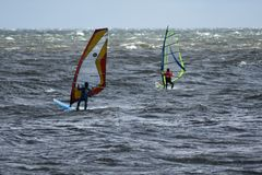 Tillbaka sikt av två surfare i handling i stormigt väder royaltyfri foto