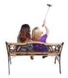 Tillbaka sikt av två kvinnor som gör en selfie att klibba ståendesammanträde på bänken Royaltyfri Fotografi