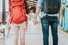 Tillbaka sikt av unga handelsresandepar med ryggsäckinnehavhanden på drevstationen Royaltyfri Foto