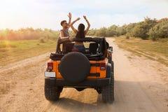 Tillbaka sikt av vänner som sitter i en bil med lyftta händer arkivfoton