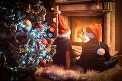 Tillbaka sikt, bärande jultomten för syskongrupp som hattar värme bredvid en spis i en vardagsrum som dekoreras för jul royaltyfria foton