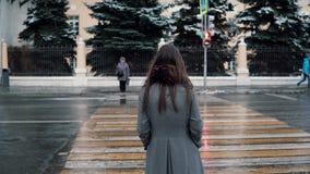 tillbaka sikt Den ledsna unga brunettflickan väntar klartecknet för att korsa vägen i vintern snö-täckt stad Royaltyfri Fotografi